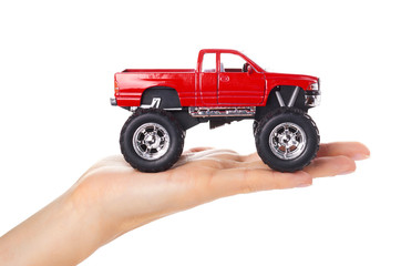 big metal red toy car offroad with monster wheels in hand isolated on white background
