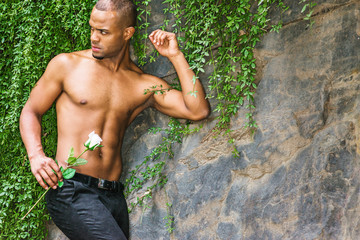 I missing you and waiting for you. Young Hispanic American man with short hair, little beard, half naked, standing by rocks with green leave plants, holding white rose, looking around,.