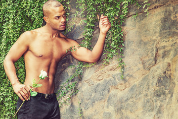 I missing you and waiting for you. Young Hispanic American man with short hair, little beard, half naked, standing by rocks with green leave plants, holding white rose, looking around..
