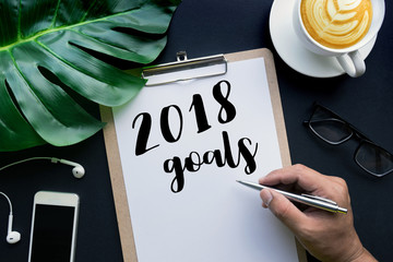 2018 goals concepts with hand writing on notepaper and business accessories laying on black table.flat lay