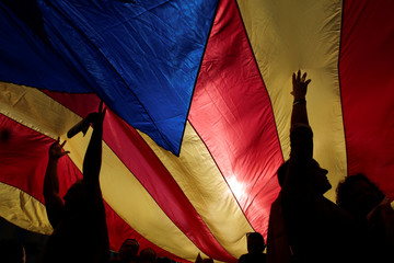 People hold a giant Catalan separatist flag during a demonstration organised by Catalan pro-independence movements ANC (Catalan National Assembly) and Omnium Cutural, following the imprisonment of their two leaders, in Barcelona