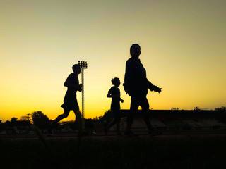 Silhouette teen age run together  track.