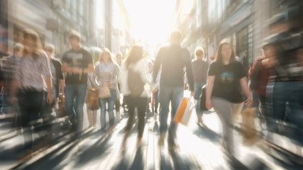 Fototapete - crowds of people in motion blur crossing a city street at sunset