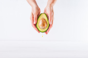 Fresh avocado with oil drop in female hands on the white background isolated. Healthy, natural beauty concept. Front view. Space for text.