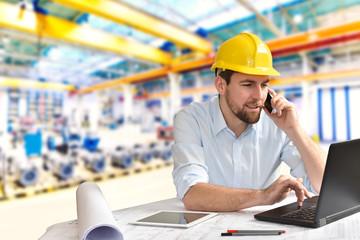 Ingenieur im Maschinenbau telefoniert am Arbeitsplatz/ Schreibtisch in einer Fabrikhalle und arbeitet am Rechner