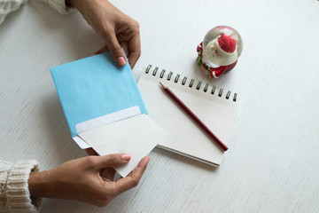 Hands with a pencil, notebook and an envelop for letter. A girl is ready to send a letter with wishes to Santa Claus. Christmas mood is to write letter or to draw a picture to make dreams come true.