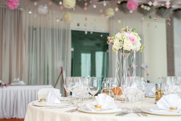 Beautiful wedding floral decoration on a table in a restaurant.White tablecloths, bright room.
