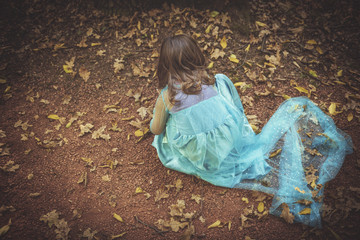 Lonely little girl playing in the wood
