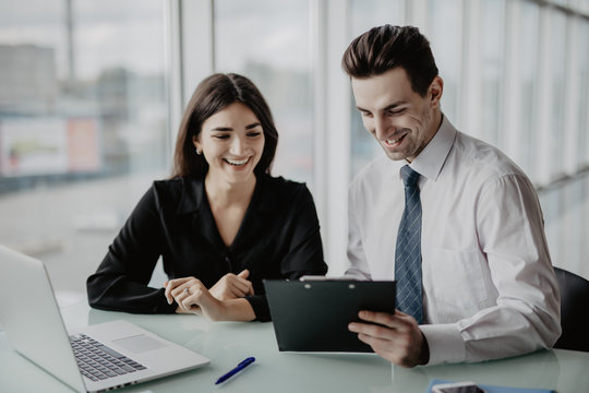Two entrepreneurs sitting together working in an office desk comparing documents. Office work.