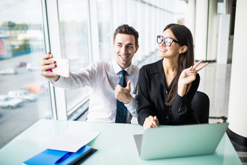 Two business people taking a Selfie in the office. Work and selfie.