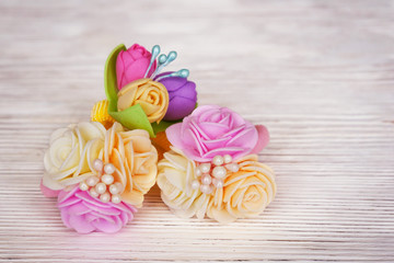 Flowers of FoamIran. Hair ornaments elastic bands on a wooden table. In a retro style.
