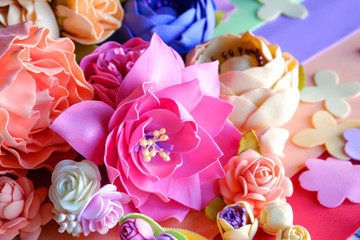 Flowers of FoamIran. Hand Made flowers. The material of the workpiece. On wooden background.