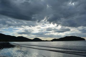 Nascer do sol em céu tempestuoso, com montanhas ao fundo na praia e reflexo do céu na água