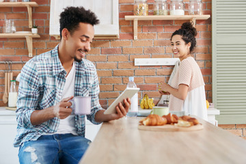Positive man reads pleasant news on tablet computer as drinks milk and croissants, shares it with wife who listens to him attentively and has happy expression, cuts fruit, spend time at kitchen