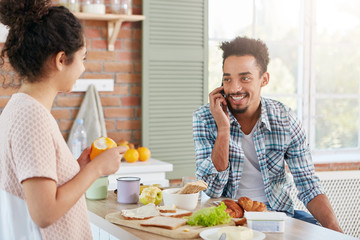 Portrait of dark skinned man has beard and mustache calls his friend as wants to invite him for lunch, looks on his wife with love. Family couple have breakfast at kichen. Everyday life concept
