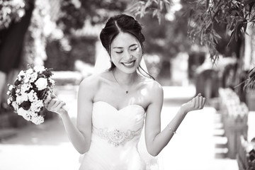 asian bride rejoicing with bouquet in hand