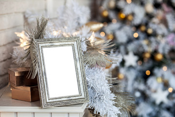White empty photo frame on the fireplace. Christmas white interior background with bokeh defocused effect
