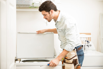 Handyman inspecting a washer