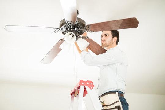 Man in ladder fixing ceiling fan