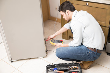 Electrician checking voltage on fridge
