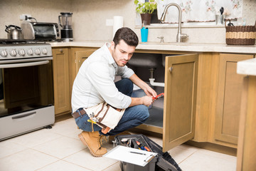 Male plumber fixing a kitchen sink