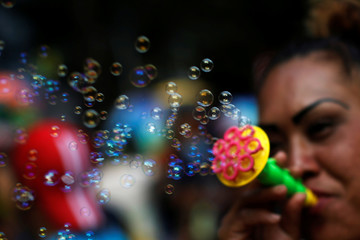 A woman blows bubbles during the annual Monumental Alebrijes Parade in Mexico City