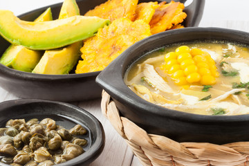 Traditional Colombian ajiaco served with patacon, avocado and capers