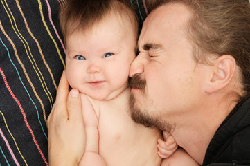 Lovely portrait of father and his little daughter. Happy fatherhood. Young dad with beard and his little baby girl