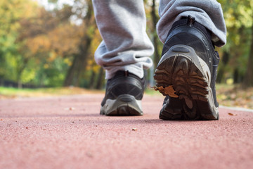 A young man in trainers and sneakers is walking along the running track