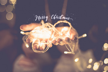 Merry christmas glowing word over hand with party light  string bokeh in vintage filter,Holiday, new year season.