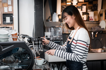 Asia female Barista wear apron making hot coffee menu for customer at counter bar,smiling Owner coffee business concept,food and drink service.