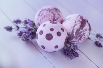 bath bombs with lavender extract. lilac bombs  and twigs of lavender on a blue wooden plank...