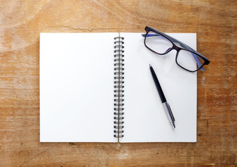 white book is placed on a wooden table. There are pens and glasses placed with a wooden floor background.