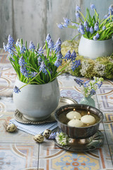 Bouquet of muscari flowers (grape hyacinth) and bowl with water and floating candles