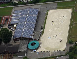 Luftaufnahme des mit Solarzellen belegten Dachs einer Reithalle mit nebenliegendem Reitplatz mit zwei Reitern