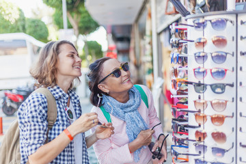 Stylish and beautiful mature mother and adult daughter travel together, walk along the street and try on eyeglasses. Family, travel, shopping, joy, communication