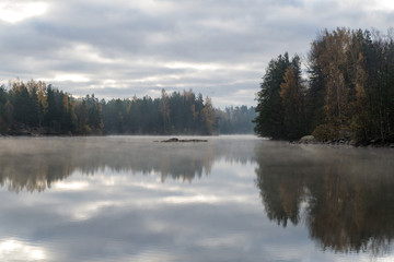 Calm lake in misty morning.