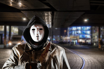 a masked man stands with a bloody knife at night in a city