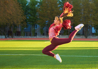 Cheerleading girl on a training jump in the morning at dawn on a field outdoors. Sport, health, fitness