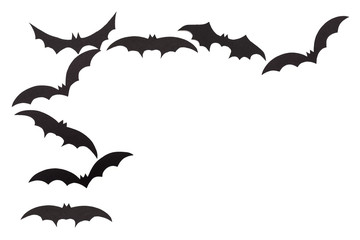 Silhouettes of volatile bats carved out of black paper are isolated on white