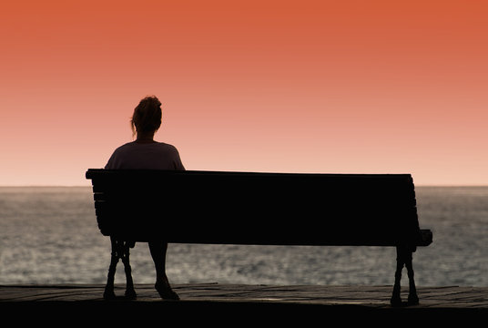 Silhouette of woman sitting alone on the bench in front of the sea