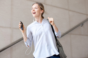 Excited carefree female intern listening to music