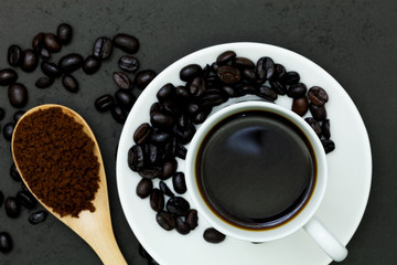 cup of coffee and coffee beans with wood spoon on black wooden table.