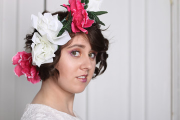 young brunette woman with clean skin, make-up and flower wreath in her hair stands near white door, three quarters