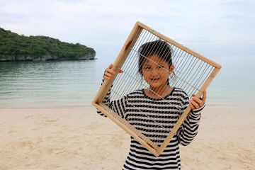 Asian girls with a steel mesh frame on the beach