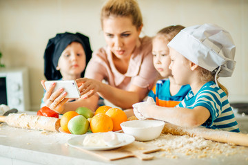 Happy family using mobile phone to find a recipe for cooking
