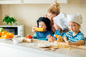 happy family in kitchen. mother and children preparing the dough, bake cookies