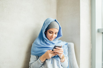 Young woman sitting and holding mobile phone