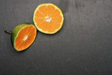 green Mandarin slices on black background