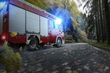 Löschfahrzeug im Herbstwald bei nasser Straße